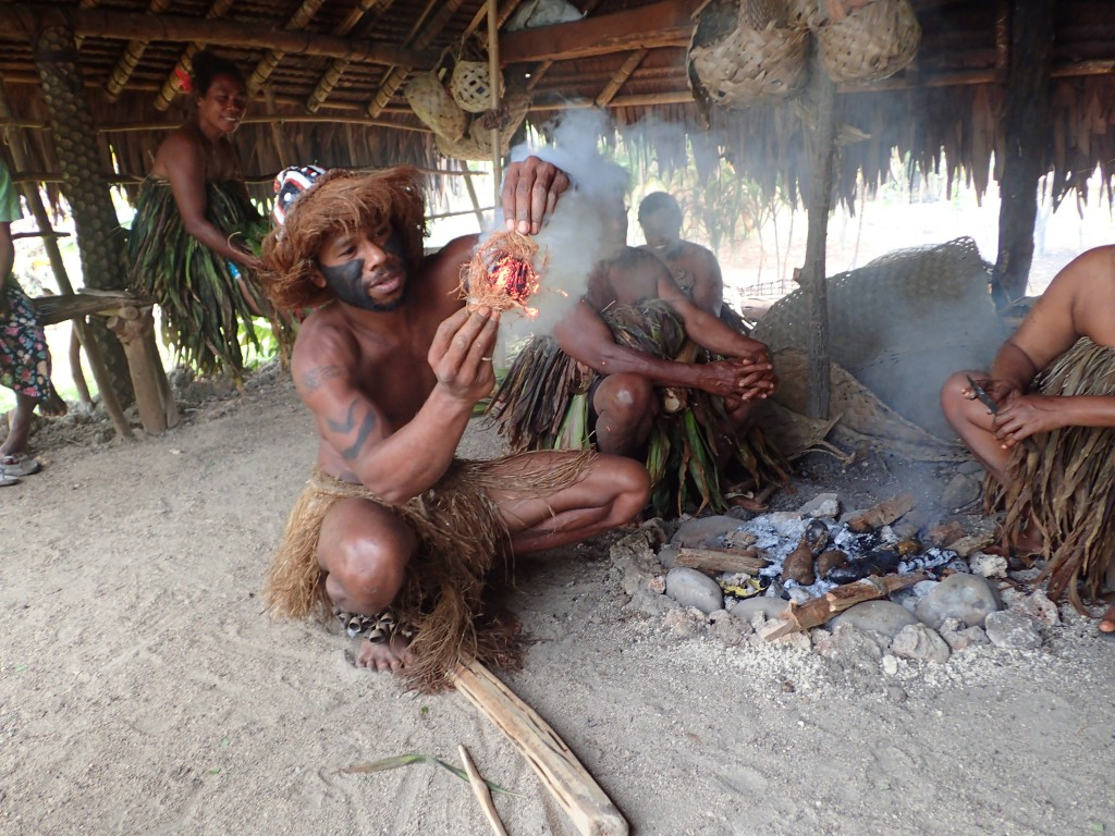 Making fire by rubbing on the stick, then catching the embers in coconut fibre
